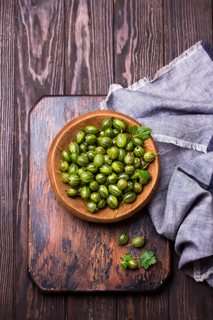 Sweet fresh gooseberry berry in a bowl on dark wooden desk. top view