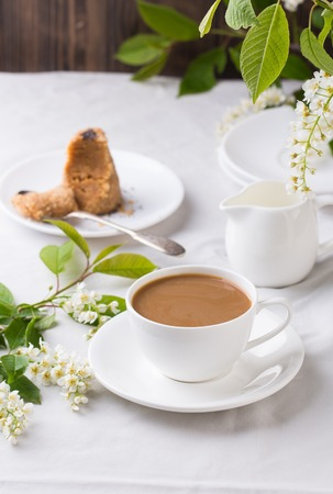 Creamy Coffee in white mug with tree blossom on pure white table