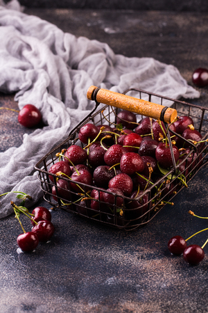Fresh sweet cherries bowl with leaves in water drops on stone Stock Photo