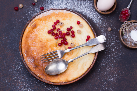 Cottage cheese casserole baked with red currant. Curd casserole with fresh berries on kitchen table. Stock Photo