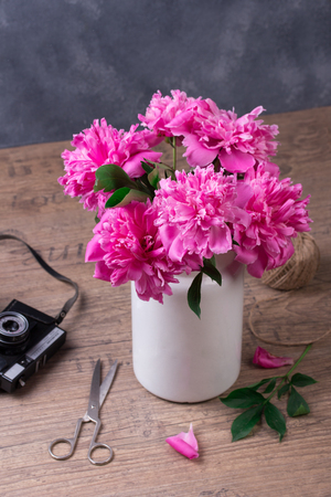 Beautiful pink peony flowers and vintage camera on grey table