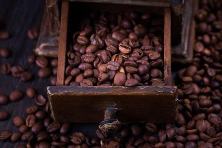 Roasted coffee beans in a vintage coffee grinder.