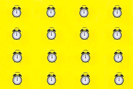 Many black classic style alarm clock isolated on yellow 版權商用圖片
