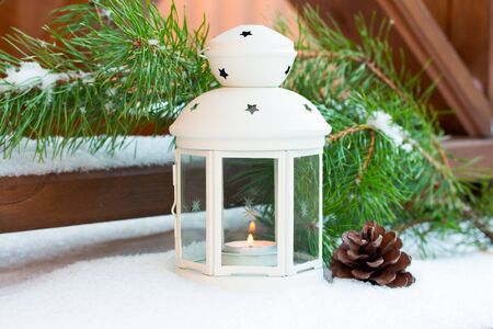 White Christmas lantern in snow with  candle light, on wooden