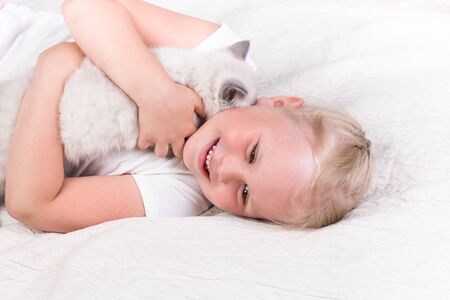 funny little girl playing with kitten on sofa