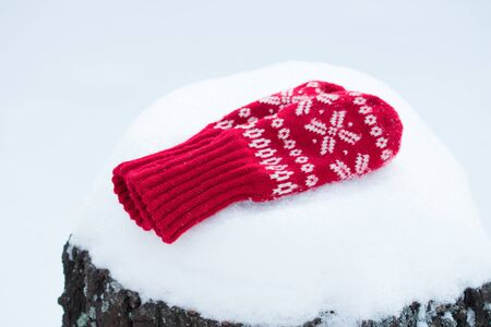 Soft warm red knitted snowflake mittens with on the white snow
