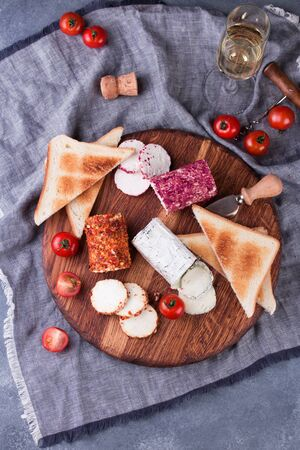 Toasts with tomatoes, goat cheese and basil on a wooden table with a glass of wine.