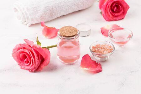 SPA treatment set with sea salt, rose aroma oil and towel roll. White background 版權商用圖片
