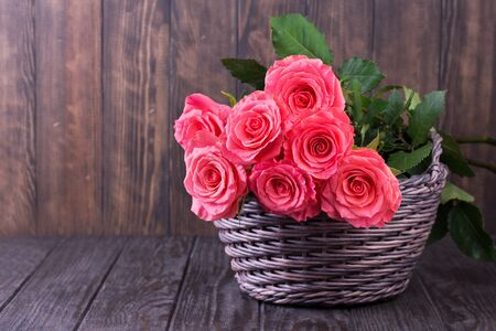 Pink roses in basket over wooden table. Valentines day background. Top view with copy space 版權商用圖片