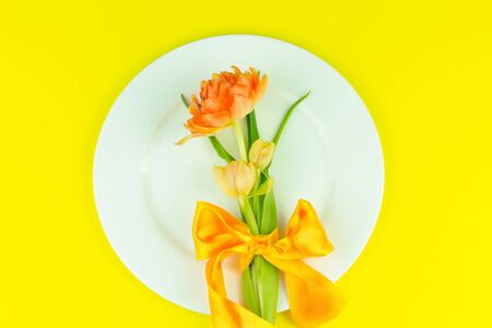 Beautiful yellow tulips in round plate on yellow background. Minimal concept. Flat lay. Mother day concept 版權商用圖片