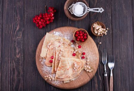 Delicious Crepes Breakfast over a vintage wood background. An healthy meal of Pancakes with sugar powder, red and white currant.