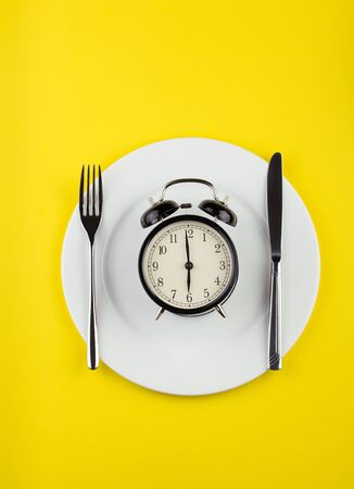 Image of alarm clock on plate, with fork and knife. Yellow background. Flat lay. Weight loss or diet concept.