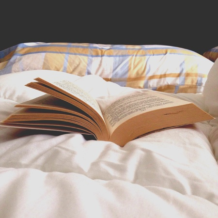 pillows: The pleasure of reading a book in bed Stock Photo