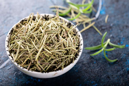 Dried rosemary in a bowl with fresh rosemary twigs.