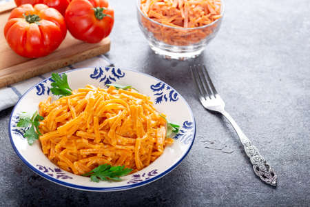 Red colored homemade traditional tomato pasta or noodles.