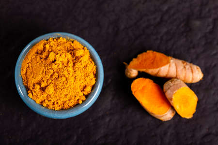 Food and drink, diet nutrition, health care concept. Raw organic orange turmeric root and powder, curcuma longa on a grunge cooking table. Indian oriental low cholesterol spices