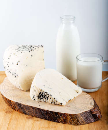Cheese with black cumin seeds with bottle of milk on wooden background.