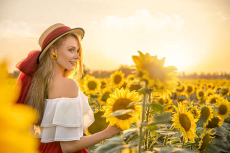 Portrait of young, happy blonde hair girl is standing in a sunflower field.