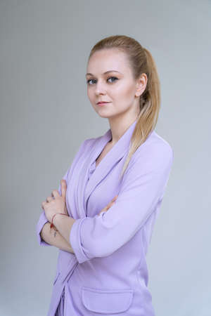 Young elegant woman, model in stylish purple suit is posing. Grey background. Banque d'images