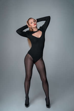 Young elegant woman, model in bodysuit and tights is posing. Grey background. Banque d'images