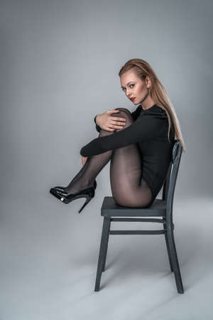 Young elegant woman, model in bodysuit and tights is sitting on a chair.