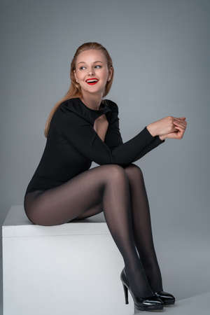 Young elegant, smiling woman, model in bodysuit and tights is sitting. Banque d'images