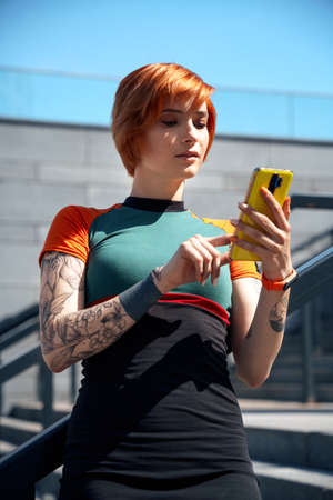 Ginger hipster, girl in a stylish dress is using an app on a smartphone outside.
