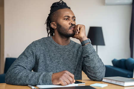 Millennial African American freelance blog writer thinking about new post