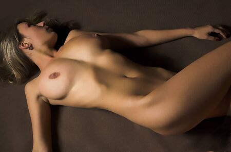 The beautiful naked girl lays on a dark background Stock Photo