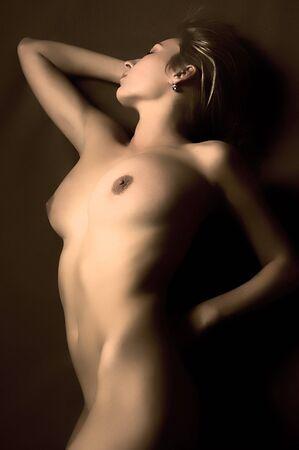 ni�a desnuda: La muchacha desnuda hermosa pone en un fondo oscuro
