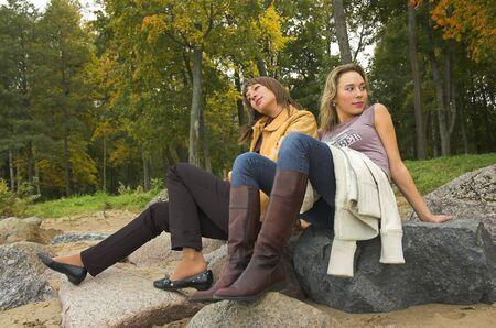 Two girls having a rest in autumn park photo