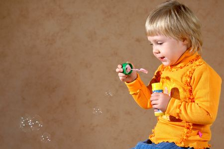 The little girl starts up soap bubbles photo
