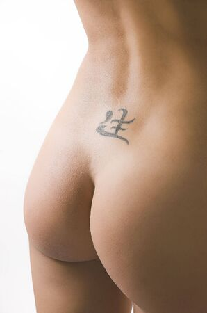 naked woman back: Female waist with a tattoo close up