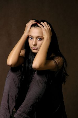 The sad beautiful girl on a dark background