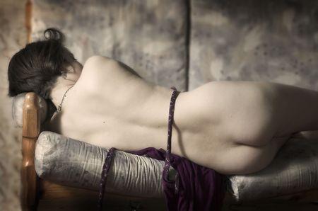 The young nude woman sleeps on a sofa Stock Photo