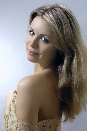 The beautiful young blonde on a grey background photo