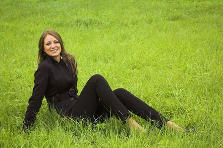 The beautiful girl sits on a green grass photo