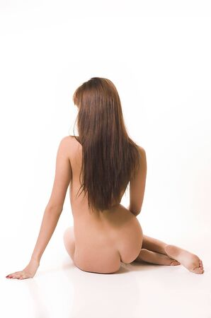 The beautiful naked girl sits on a white background Stock Photo