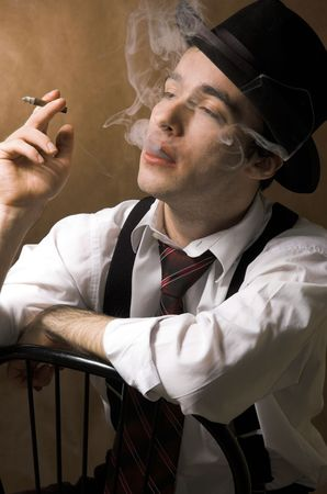 The man in a hat smokes a cigar
