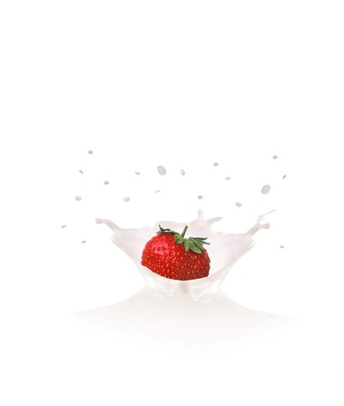 Strawberry falls into milk causing splash and drops photo