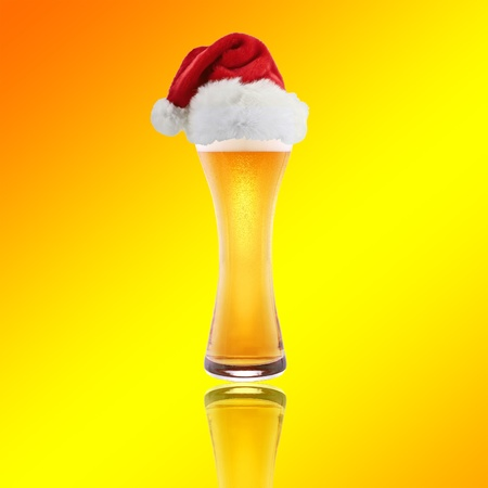 Beer and hat of Santa Claus on a yellow background photo