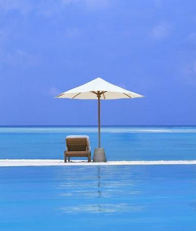 silla playa: Sillas de playa y paraguas en una bella isla Foto de archivo