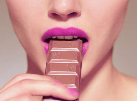 Closeup of smiling woman eating chocolate bar photo