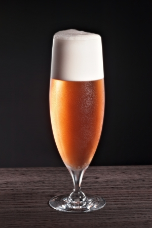 Beer into glass on a black background Stock Photo - 14060518
