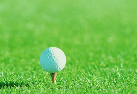 Golf ball on tee over a blurred green  photo