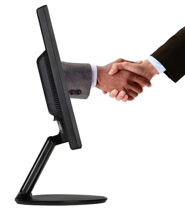 Businessmen shaking hands out of TV screen photo