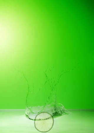 lime in the water splash on green background