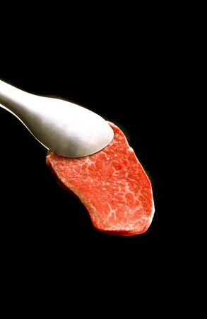 piece of meat on a fork isolated on black background photo