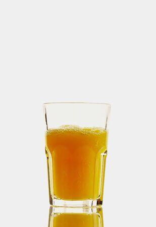 Glass with orange juice isolated on the white photo