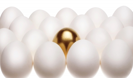 carbonate: one gold egg lays among common white eggs Stock Photo